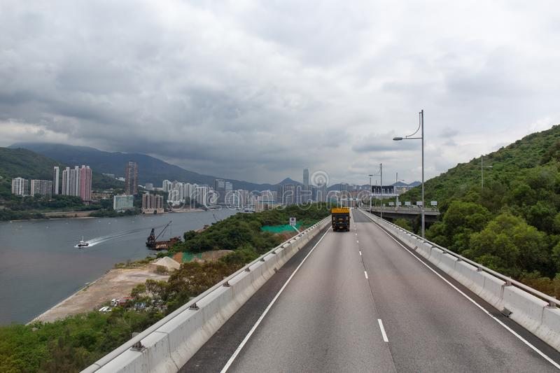 Tsing Yi North Coastal Road in Tsing Yi island connect to New Te. Rritories in Hong Kong from double decker bus view with sea mountain rang and city background stock image