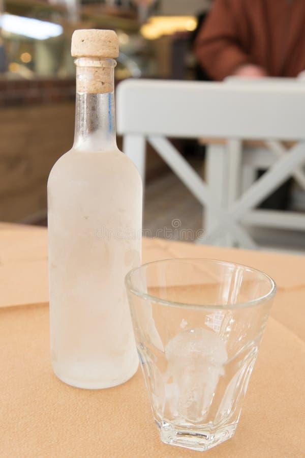 Tsipouro con un vetro con ghiaccio fotografia stock