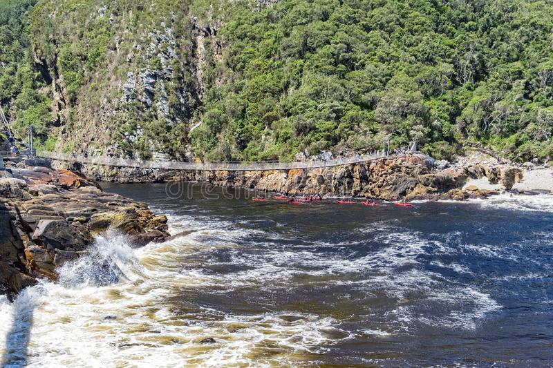 Tsitsikamma storms river suspension bridge. With people kayaking under the bridge royalty free stock photo
