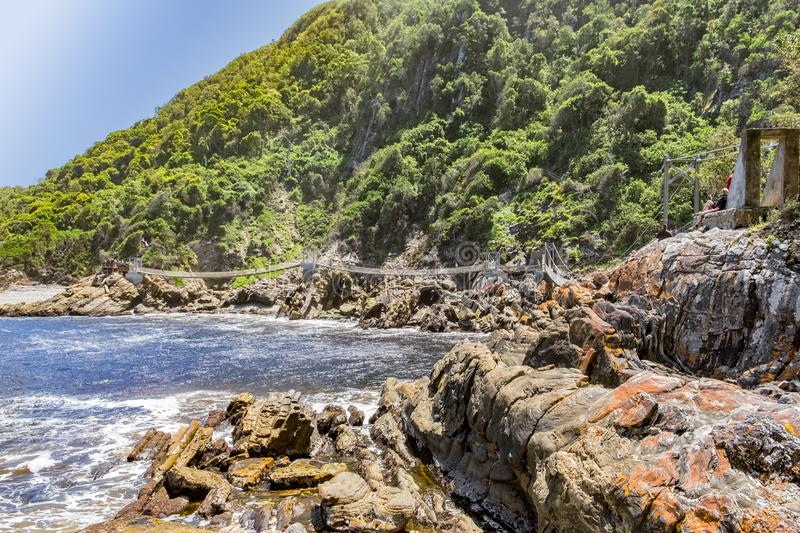 Tsitsikamma storms river suspension bridge. With unrecognizable people walking on it stock image