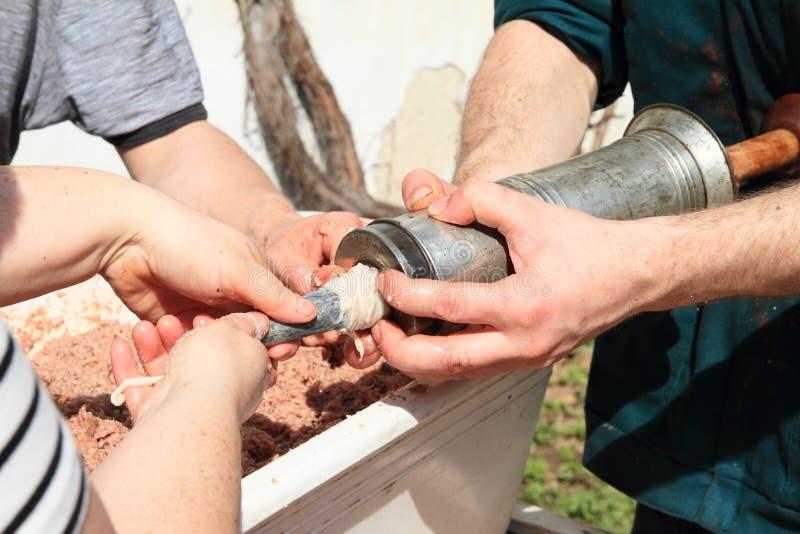 Tsjech schuifelt - het vullen varkensvleesknoeiboel in darmen stock afbeeldingen