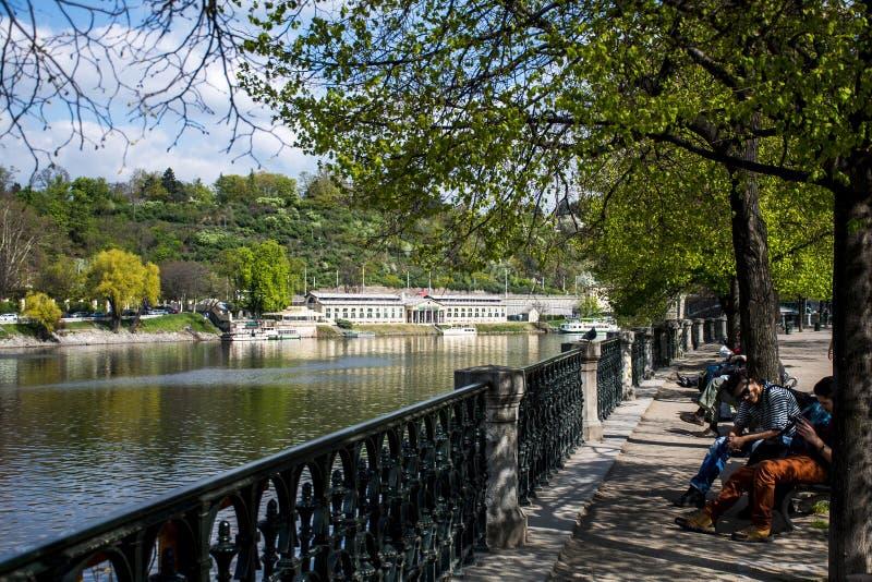 Tsjechische Republiek Praag 11 04 2014: Mening van paleis en Vltava-Rivier met mensen bij een Tsjechische Republiek van parkpraag royalty-vrije stock fotografie