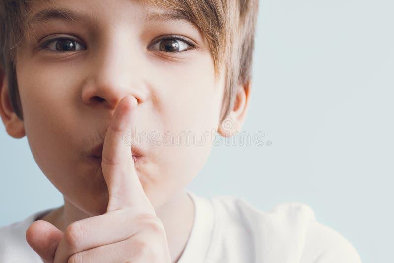 Tsss! Το αγόρι παρουσιάζει χειρονομία ότι πρέπει να τηρήσετε τη σιγή στοκ φωτογραφία
