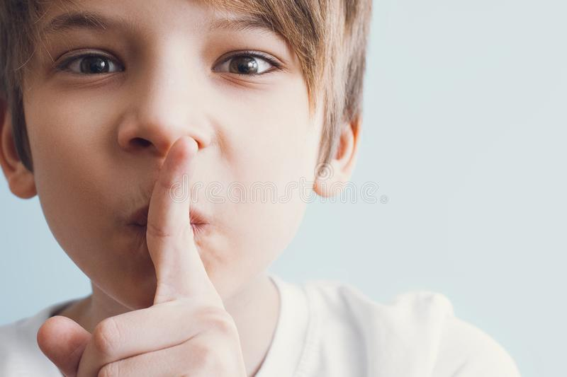 Tsss! Boy shows gesture that you need to observe silence. Emotion concept stock photography