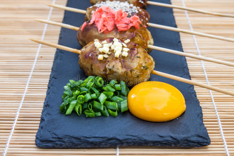 Tsukune - Japanese chicken yakitori meatballs served with chili sauce, flakes, ground pepper and lemon wedges. Tsukune - Japanese chicken yakitori meatballs stock photos