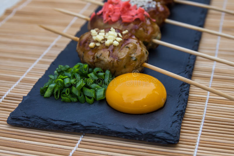 Tsukune - Japanese chicken yakitori meatballs served with chili sauce, flakes, ground pepper and lemon wedges. Tsukune - Japanese chicken yakitori meatballs stock photography