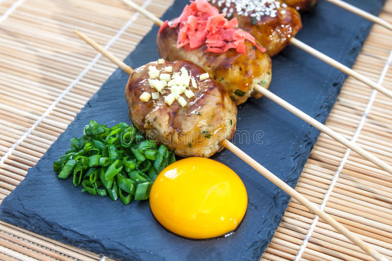 Tsukune - Japanese chicken yakitori meatballs served with chili sauce, flakes, ground pepper and lemon wedges. Tsukune - Japanese chicken yakitori meatballs royalty free stock photo