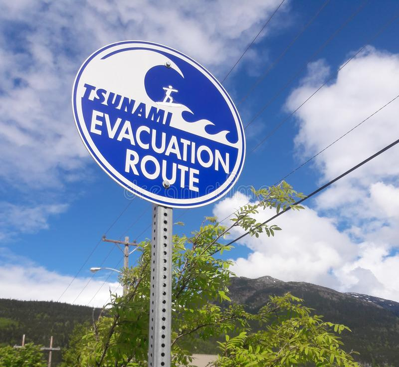 Tsunami Evacuation Route blue sign with surfer riding wave. Alaska, skagway, street, surfing, sticker, funny stock photos