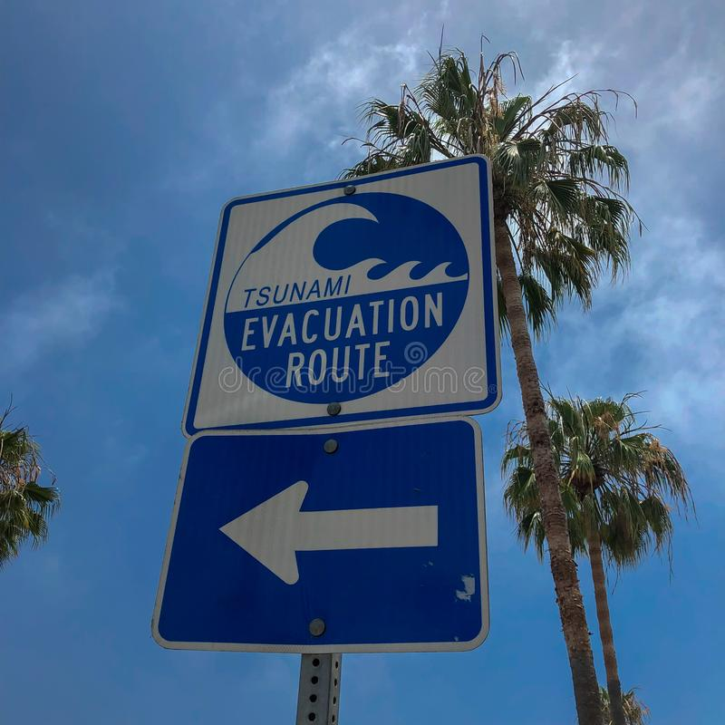 Tsunami evacuation route sign in Venice Beach. California, USA. Evacuation route at danger of a tsunami on a blue sky background with palm trees stock images