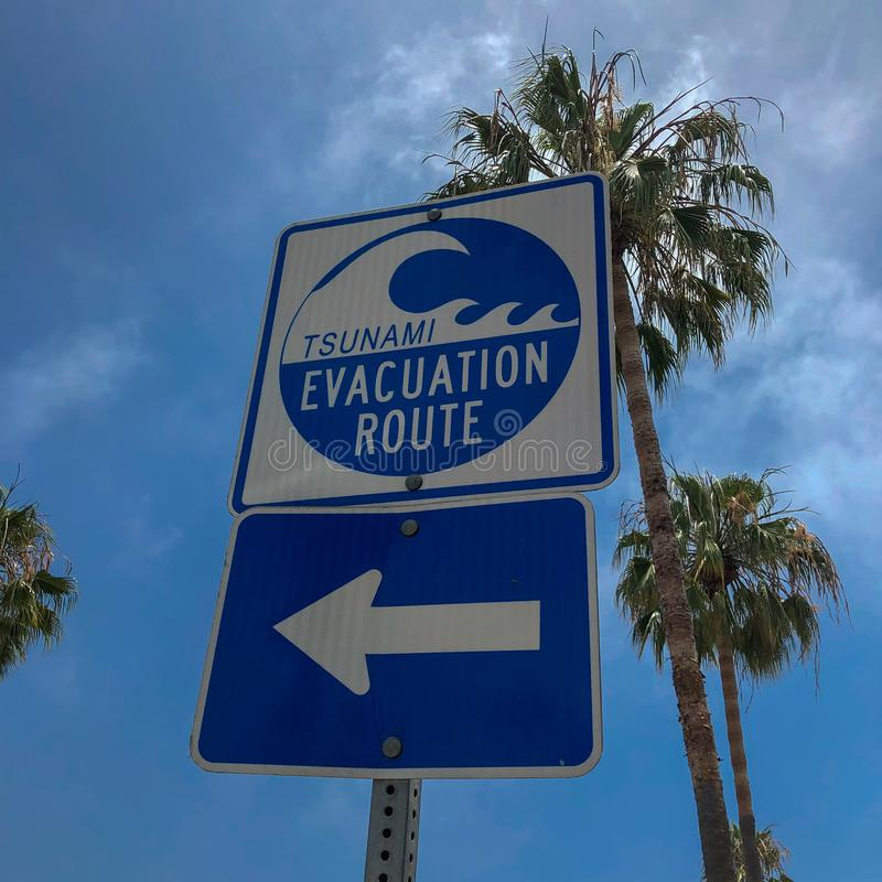 Tsunami evacuation route sign in Venice Beach. California, USA. Evacuation route at danger of a tsunami on a blue sky background with palm trees royalty free stock photos