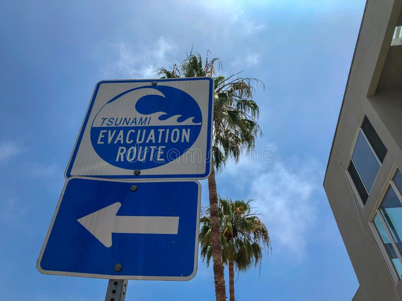 Tsunami evacuation route sign in Venice Beach. California, USA. Evacuation route at danger of a tsunami on a blue sky background with palm trees royalty free stock photo