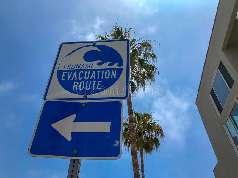 Tsunami evacuation route sign in Venice Beach. California, USA. Evacuation route at danger of a tsunami on a blue sky background with palm trees stock photos
