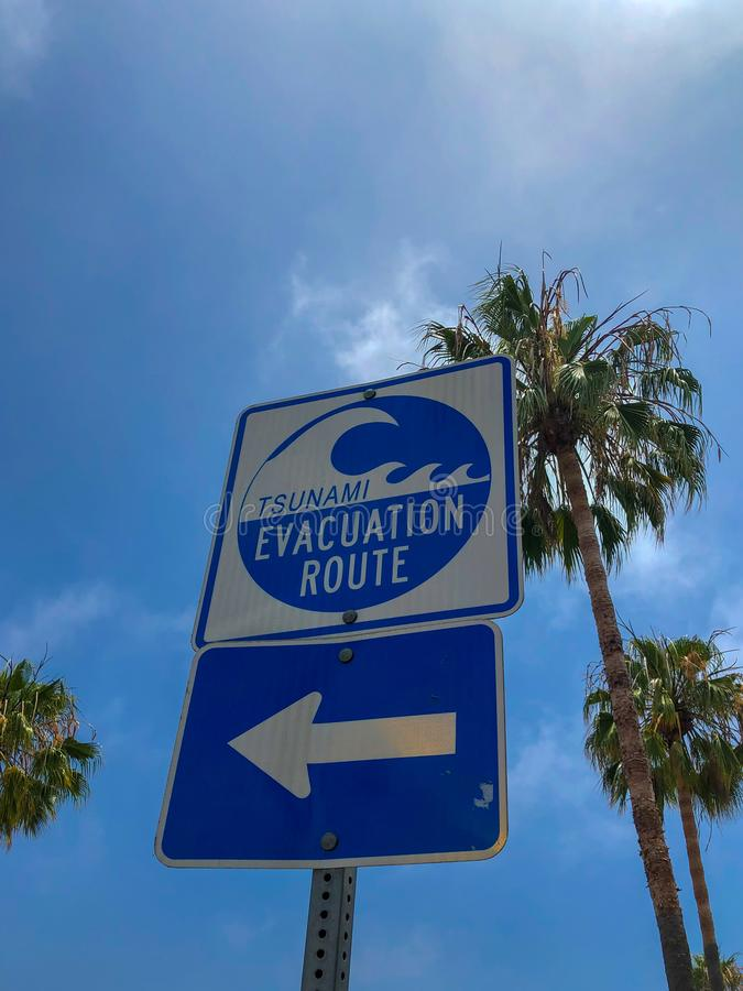 Tsunami evacuation route sign in Venice Beach. California, USA. Evacuation route at danger of a tsunami on a blue sky background with palm trees stock image