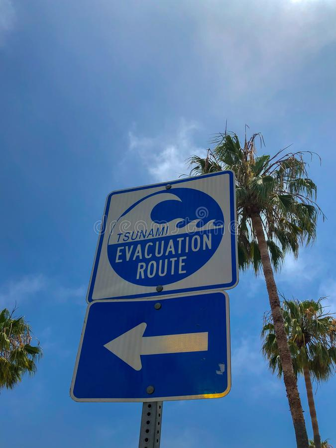 Tsunami evacuation route sign in Venice Beach. California, USA. Evacuation route at danger of a tsunami on a blue sky background with palm trees stock photo