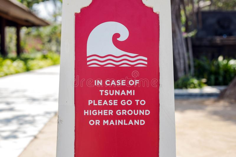 Tsunami roadsign pointing towards the stunami evacuation route, escape plam in Indonesia Bali. Red stock image