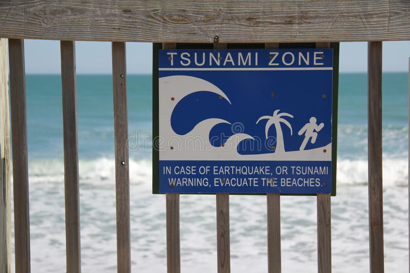 Tsunami Zone Sign. A tsunami zone sign that is attached to a wooden rail overlooking the Atlantic ocean in Florida royalty free stock photos