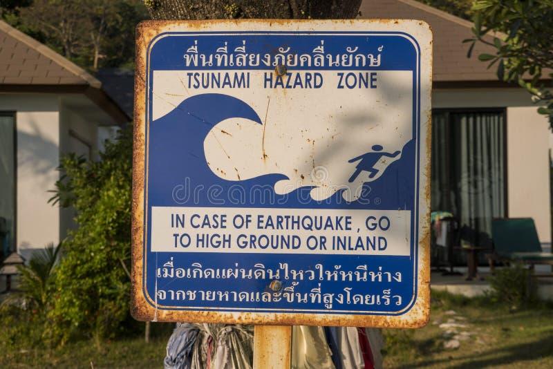 Tsunamiwaarschuwingsbord bij een strand in zuidelijk Thailand Thaise taalinstructies die mensen aan hoge grond vertellen te lopen stock fotografie