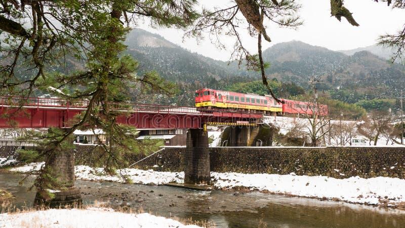TSUWANO, JAPÃO - NOVEMBRO 28,2018: Visitantes que esperam para tomar uma imagem de um trem vermelho que corre através de uma pont imagens de stock