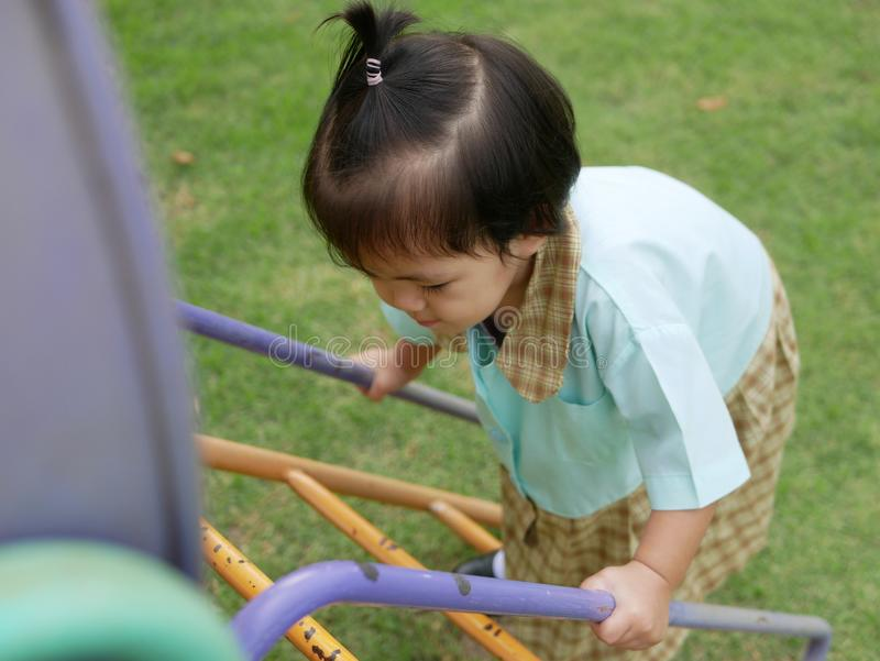 Little Asian baby girl enjoys climbing stairs at a playground. Ttle Asian baby girl, 18 months old, enjoys climbing stairs at a playground. - large muscle and royalty free stock photos