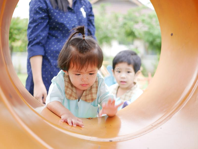 Little Asian baby girl, 18 months old, left together with her sister enjoy climbing at a playground stock images