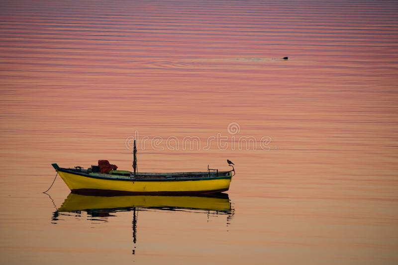 Little boat floating on the calm water under amazing sunset in Q stock photo