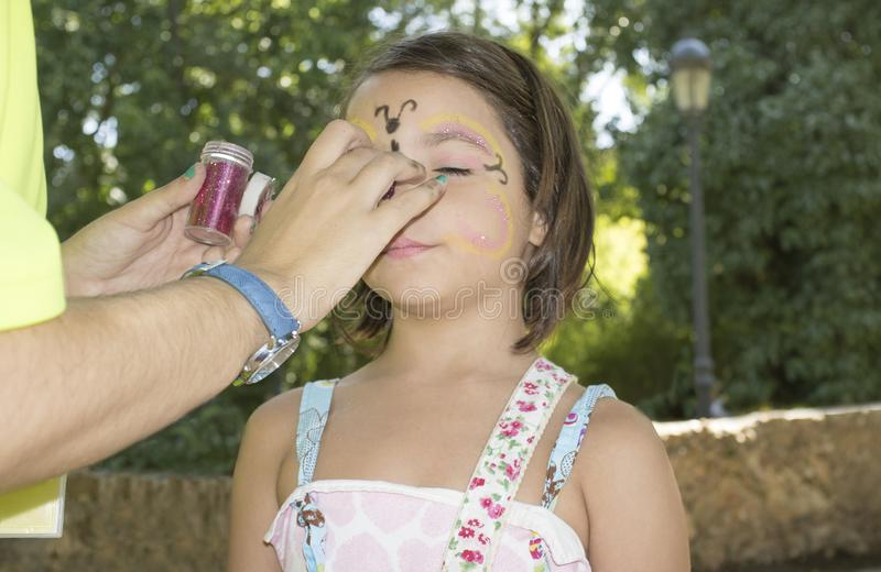 Little girl getting face painted during outdoors party. Ttle girl getting face painted during outdoors party. The make-up artist uses brilliantine stock photography