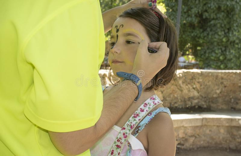 Little girl getting face painted during outdoors party. Ttle girl getting face painted during outdoors party. The make-up artist uses face paint crayons stock photography