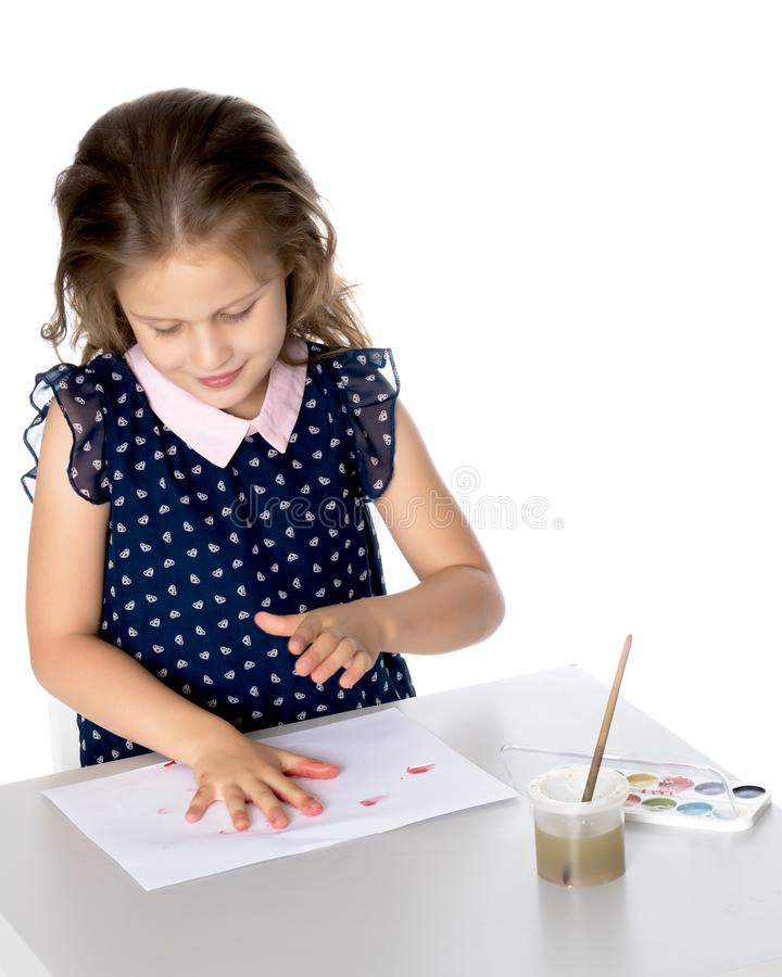 The little girl got dirty with the paints. stock images