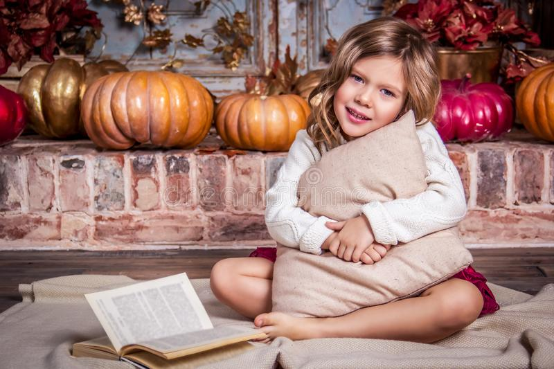 Little happy girl. Baby girl hugging pillow. Girl with pumpkins royalty free stock images