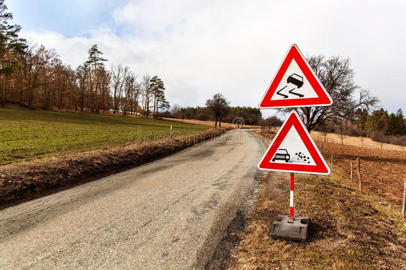 Ttraffic sign `Slippery Road` on the road background in Czech Republic. Warning sign concerning dangerous road surface. Asphalt r. Oad in the countryside stock photography
