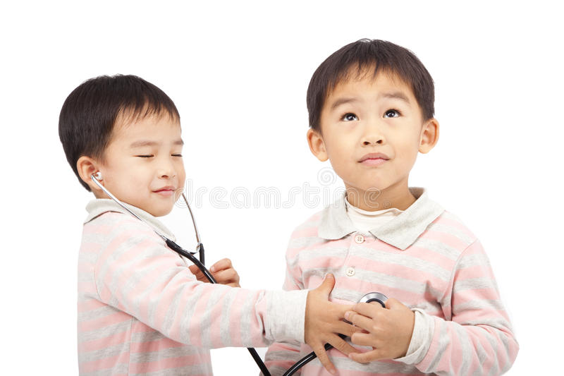 Ttwo boys using stethoscope Check. Two boys using stethoscope Check the heartbeat royalty free stock photography