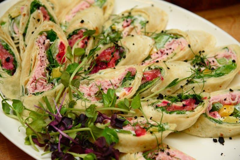 Tuńczyka opakunek ściska z szpinakami i warzywami na talerzu obrazy royalty free