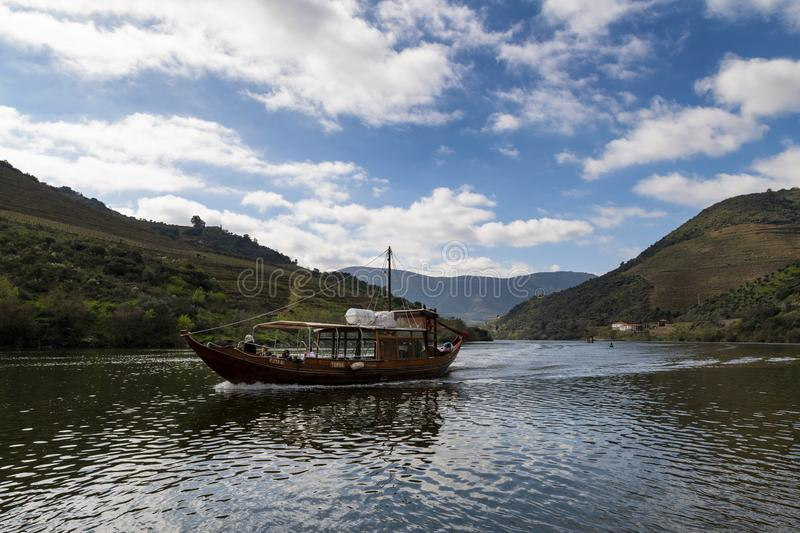 Tourists in a traditional rabelo boat at the Douro River near the village of Tua with terraced vineyards stock images