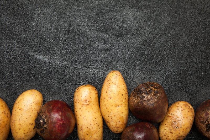 Tubérculos de la patata y de las remolachas rojas en una tabla negra Copie el espacio imagen de archivo