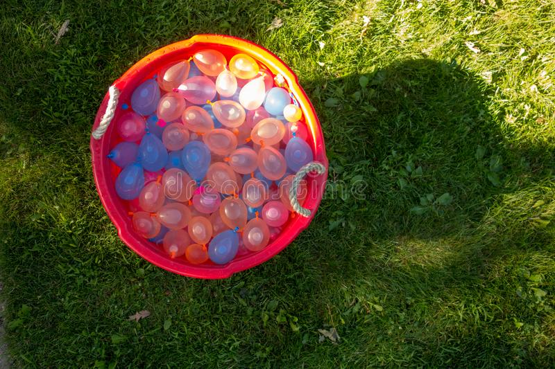A tub full of water balloons ready for summer fun royalty free stock image