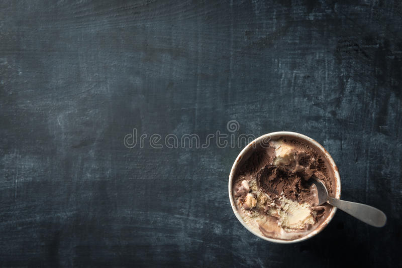 Tub of ice cream. On dark food background royalty free stock image