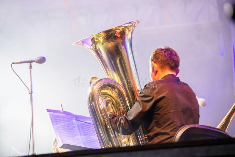 Tuba gracz w orkiestrze na scenie, sztuki na dużej mosiężnej tubce krótkopęd, za kulisami fotografia stock