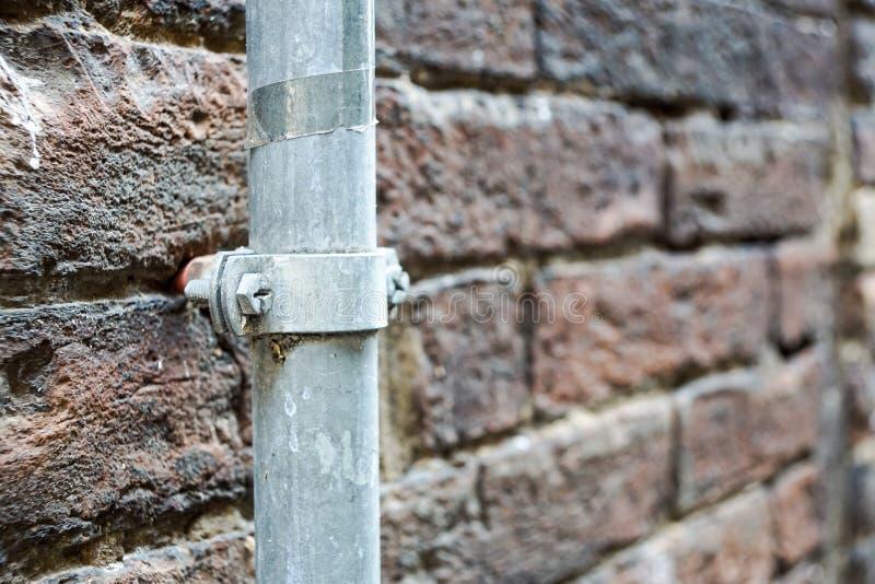 Tubatura del TUBO di EMT e scatola di giunzione metalliche elettriche sulla parete di mattoni grigia nel cantiere su costruzione fotografie stock