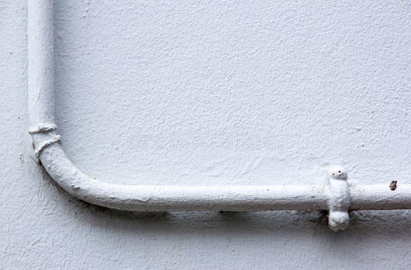 Tubatura dell'acqua dipinta montata sulla parete intonacata fotografia stock libera da diritti
