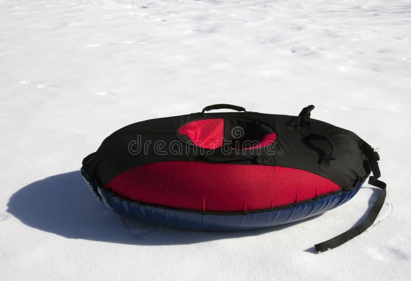 Tubatura interna della neve materiale rossa e nera (toobing) sul bianco fotografia stock libera da diritti