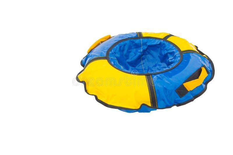 Tubatura rotonda di gomma gonfiabile della slitta dei bambini per il giro di inverno con gli scorrevoli, blu-giallo isolati su fo immagini stock