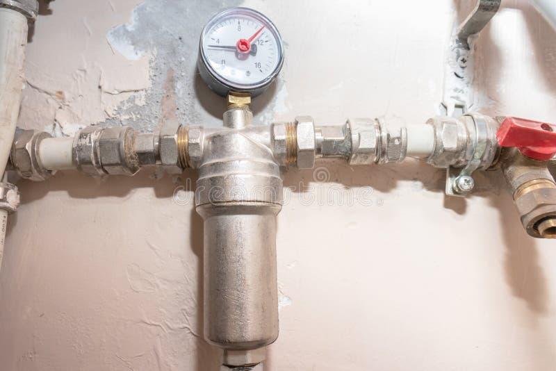 Tubature dell'acqua del metallo, rifornimento idrico in casa con il filtro, manomether, rubinetti e montaggi di distribuzione fotografie stock libere da diritti