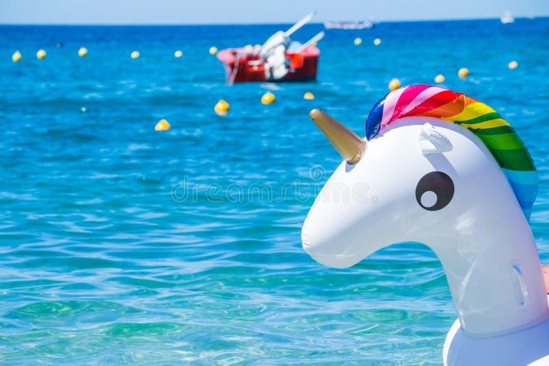Tube de bain de licorne sur la plage sur le fond de mer Licorne en caoutchouc gonflable Anneau de bain d'imagination pour le voya photo libre de droits