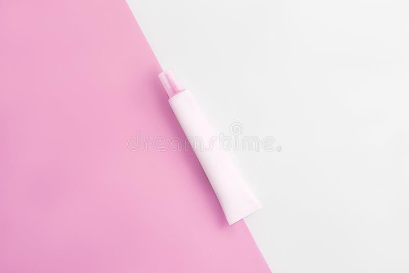Tube de cosmétiques sur le fond rose et blanc en pastel Copiez l'espace Configuration plate photos libres de droits