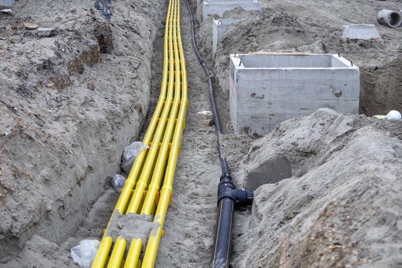 Tubería amarilla del PVC para los sistemas de cable enterrados en la arena fotografía de archivo