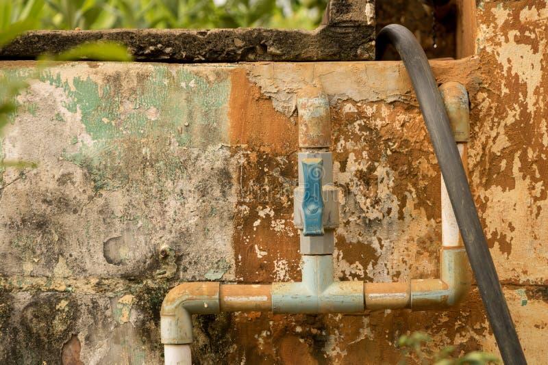 Tubería plástica del agua de la válvula azul del PVC - textura mohosa de la pared del vintage imagenes de archivo