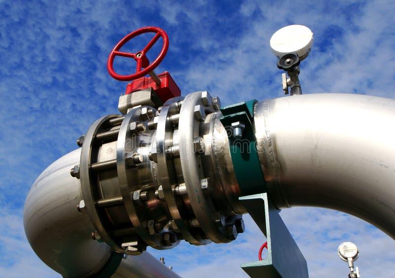 Tuberías industriales y válvulas del acero inoxidable contra el cielo azul fotografía de archivo