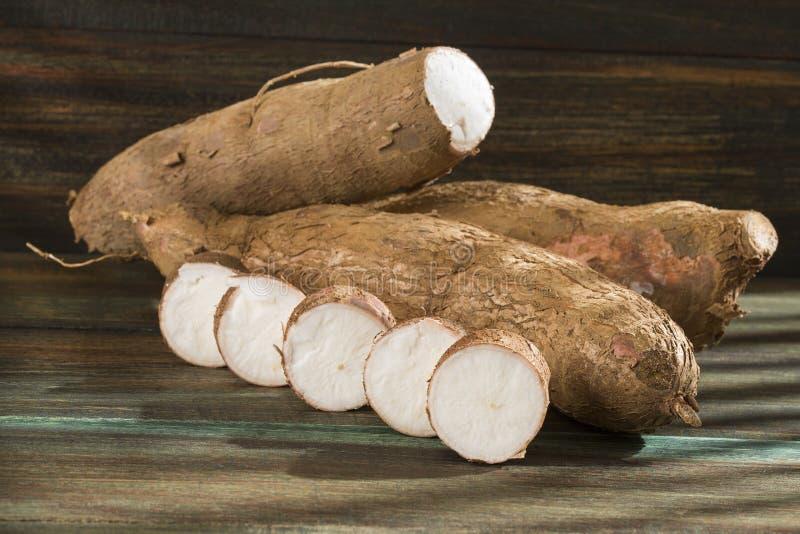 Tubercule cru de manioc sur le fond en bois - Manihot esculenta photographie stock