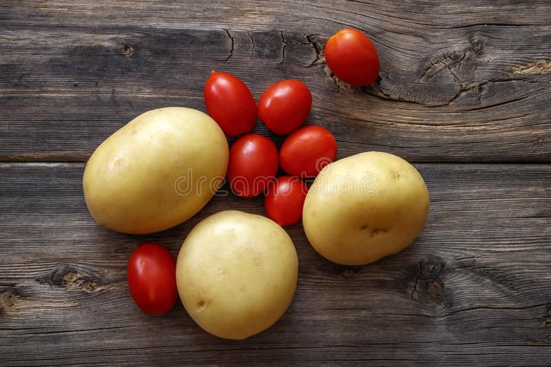 Tuberi della patata e pomodori ciliegia rossi fotografia stock libera da diritti