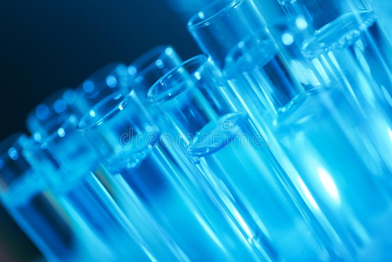 Tubes à essai avec le liquide sur le fond bleu Chimie de solution photos libres de droits